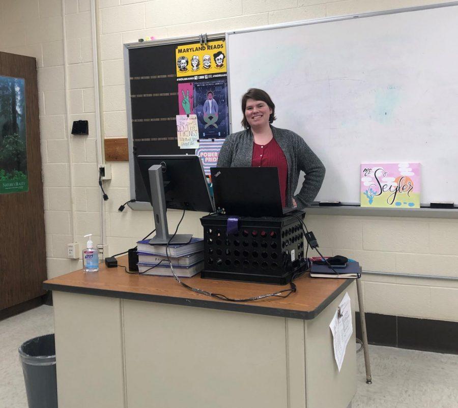 Ms.+Seyler%2C+posing+at+her+desk+in+the+school+building.+Photo+courtesy+of+Ms.+Amie+Littman