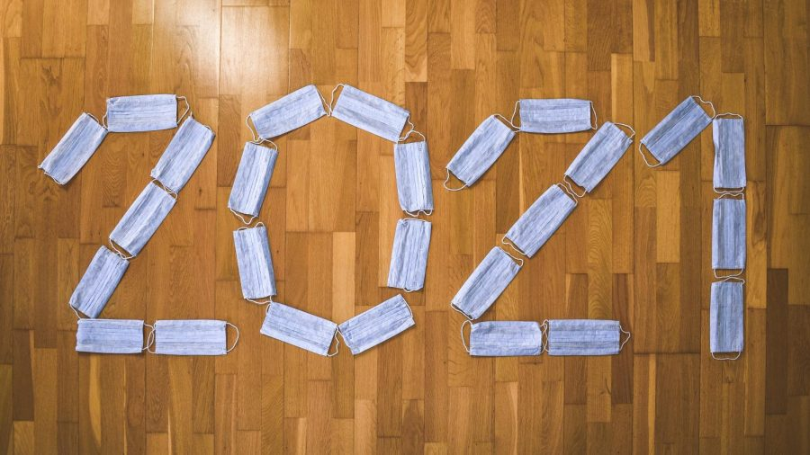 Facial masks spelling the year 2021, arranged in a horizontal position, placed out on a wooden floor.  Photo courtesy of Ibrahim Boran